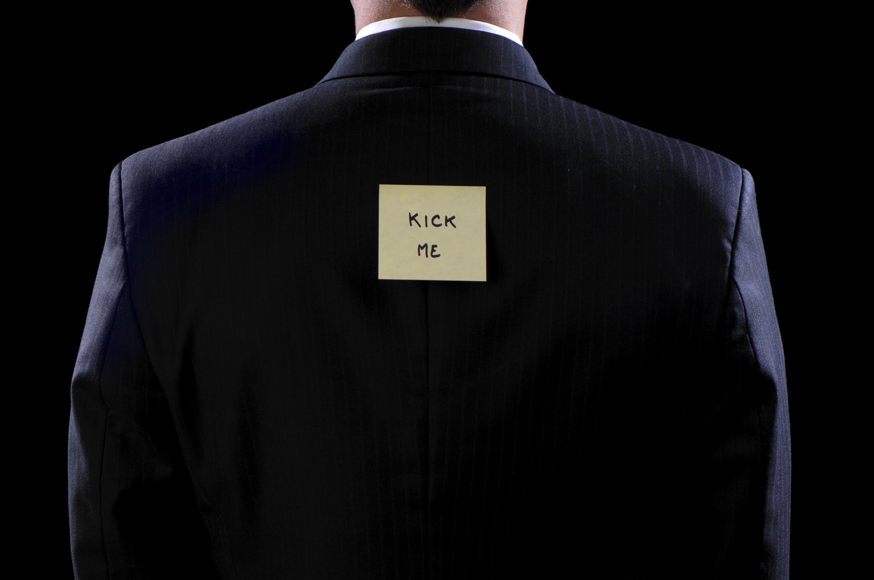 A businessman with a Kick Me sign