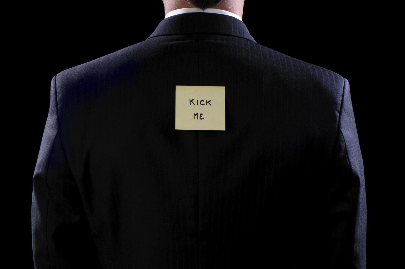 A businessman with a Kick Me sign
