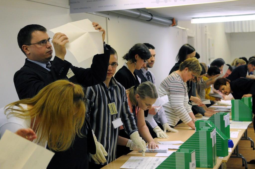 Szavazatszámlálók ellenőrzik a szavazólapokat a Nemzeti Választási Iroda budapesti székházában