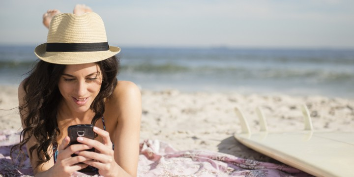 USA, New York State, Rockaway Beach, Woman using cell phone on beach