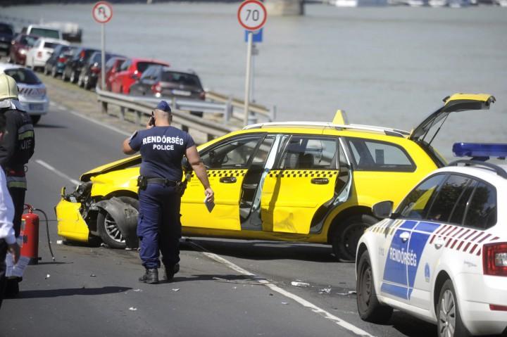 Budapest, 2016. augusztus 23. Összetört taxi a budai alsó rakparton, az Erzsébet híd közelében 2016. augusztus 23-án. A taxi sofõrjét a rendõrök igazoltatni akarták a VIII. kerületi Diószeghy Sámuel utcában. A férfi menekülni kezdett a Petõfi hídon át, majd a budai alsó rakparton több autót is megrongált. Ezt követõen a híd közelében a gépkocsi szalagkorlátnak ütközött és kigyulladt. A rendõrök a férfit az égõ autóból kiszabadították és elfogták. MTI Fotó: Mihádák Zoltán