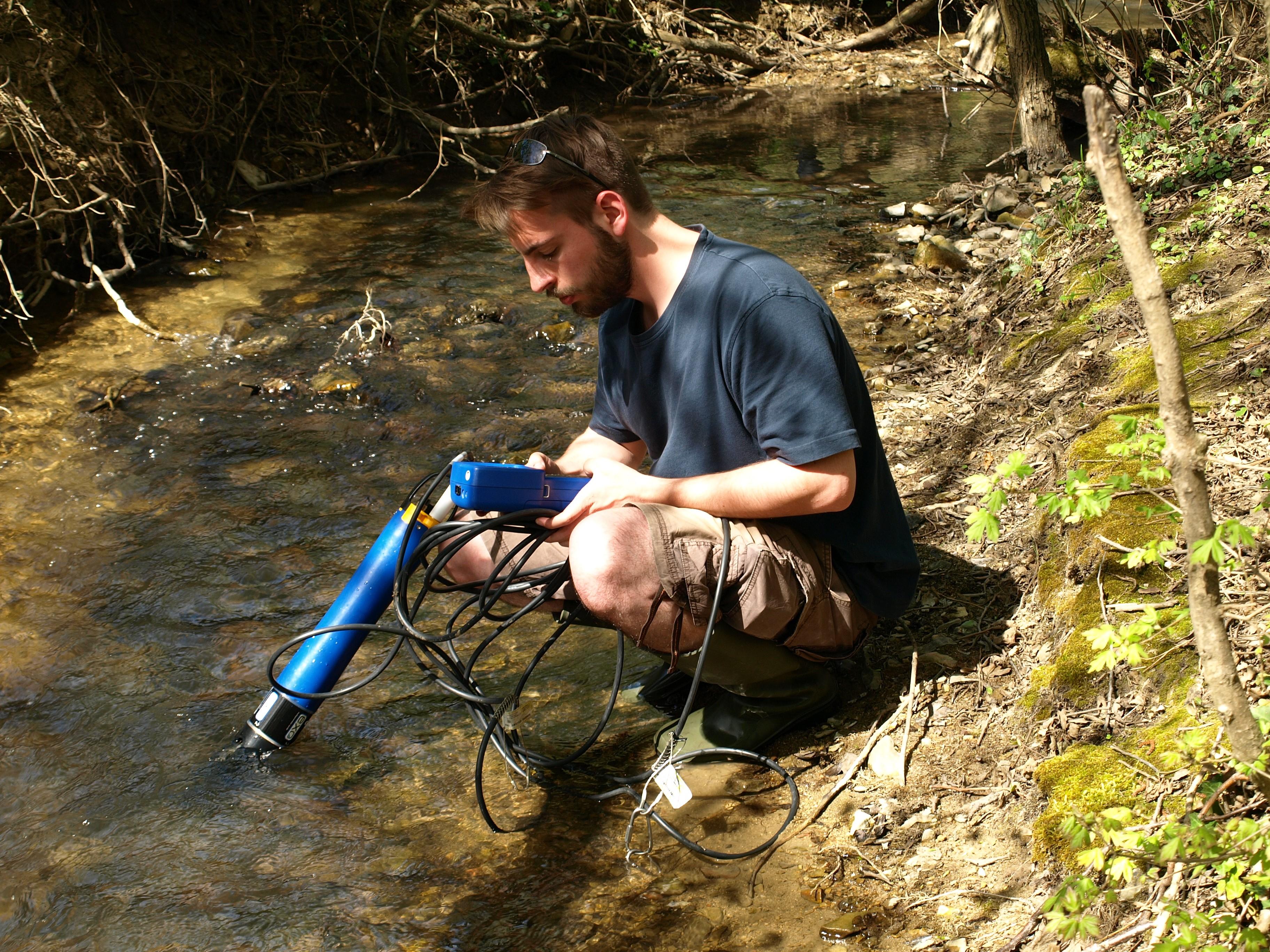 A fiatal kutató a mecseki patak vizét vizsgálja
