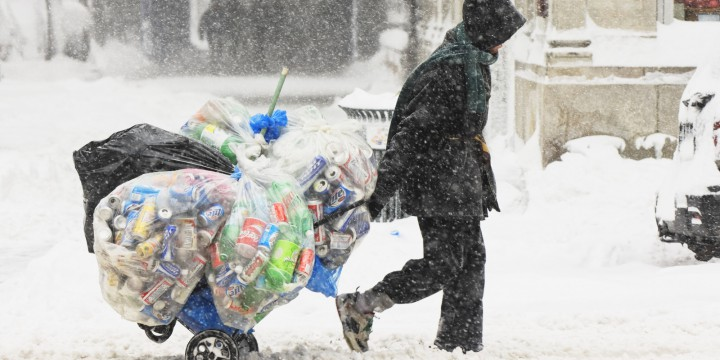 Man wheeling trolley of empty cans and bottles in snowstorm, side view