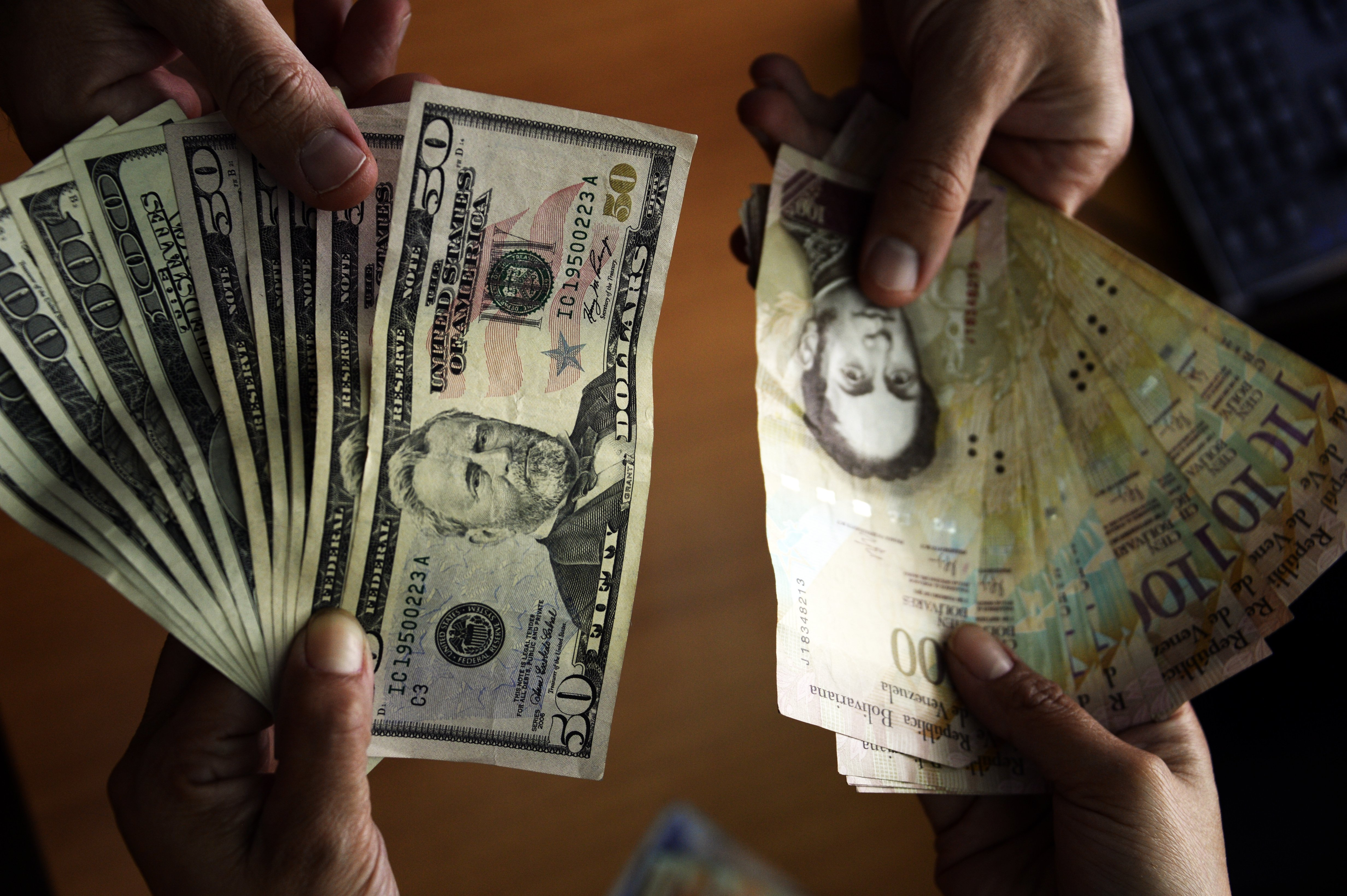 Photo showing US dollar and Venezuelan Bolivares notes in Caracas on July 16, 2013. In a country with strict currency exchange control since 2003, Venezuelans in urgent need of dollars to travel lined up on banks Tuesday --the deadline to buy dollars for the first time at an auction-- looking forward to get more currency than the allowed, despite being at a higher rate than the official.   AFP  PHOTO / JUAN BARRETO        (Photo credit should read JUAN BARRETO/AFP/Getty Images)